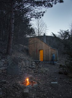 As a wilderness retreat for a songwriter, this compact, prefabricated wooden hut in Wienerwald, Austria, was designed by architects Heike Schlauch and Robert Fabach of Austrian studio raumhochrosen architekturkonzepte. They sought to create a visual and geographical connection with the woods outside. The hut's asymmetrical roof, which slopes steeply on one side, gives it a distinctly modern visage amidst a rural setting.