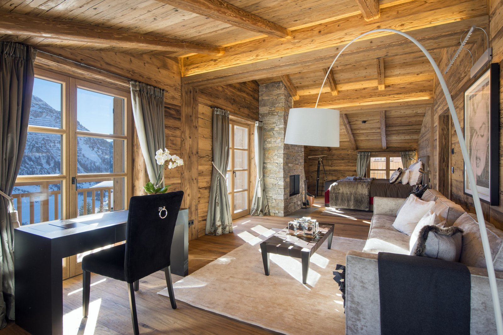 Living Room, Sofa, Floor Lighting, Coffee Tables, Medium Hardwood Floor, Rug Floor, Chair, Accent Lighting, Standard Layout Fireplace, and Desk  Photo 4 of 9 in Rent One of These Cozy Cabins For a Ski Trip This Winter