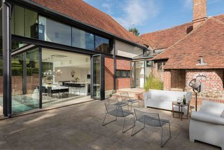 A 15th-century Tudor vacation rental in Kent, England, gets a modern update with glazing and polished steel, plus a large, sun-filled patio that's furnished with contemporary outdoor furniture.
