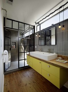 Even in small amounts, bright colors can uplift most bathrooms. In this Bay Area houseboat, architect Robert Nebolon used a teak live-edge countertop and a custom yellow cabinet supporting a double washbasin by Duravit to create a sophisticated steampunk-inspired look.