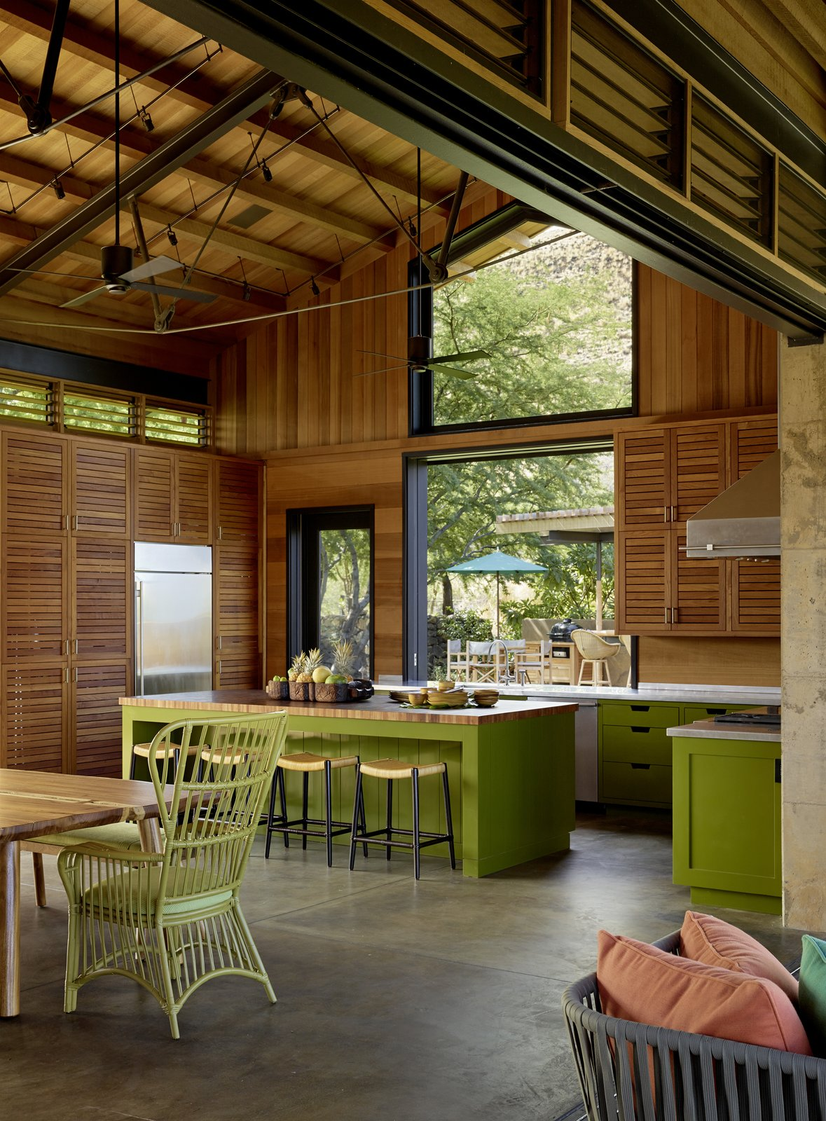 Kitchen, Marble Counter, Wood Counter, Wood Cabinet, Concrete Floor, Range Hood, Refrigerator, Wood Backsplashe, and Track Lighting  Photo 7 of 20 in An Incredible Home in Hawaii That's As Much Fun As Summer Camp