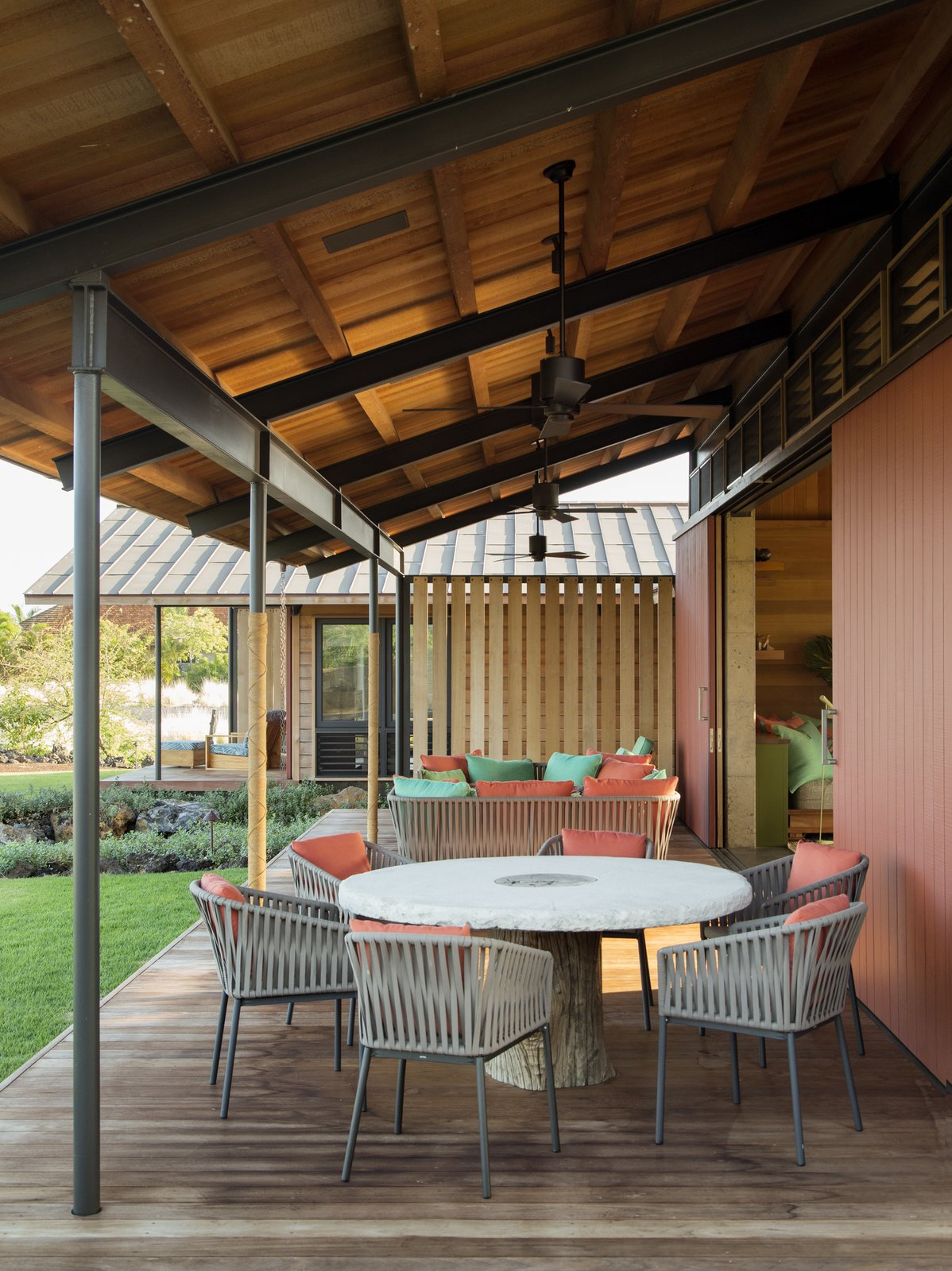 Outdoor, Back Yard, Grass, Small Patio, Porch, Deck, Wood Patio, Porch, Deck, Decking Patio, Porch, Deck, and Hanging Lighting  Photo 8 of 20 in An Incredible Home in Hawaii That's As Much Fun As Summer Camp