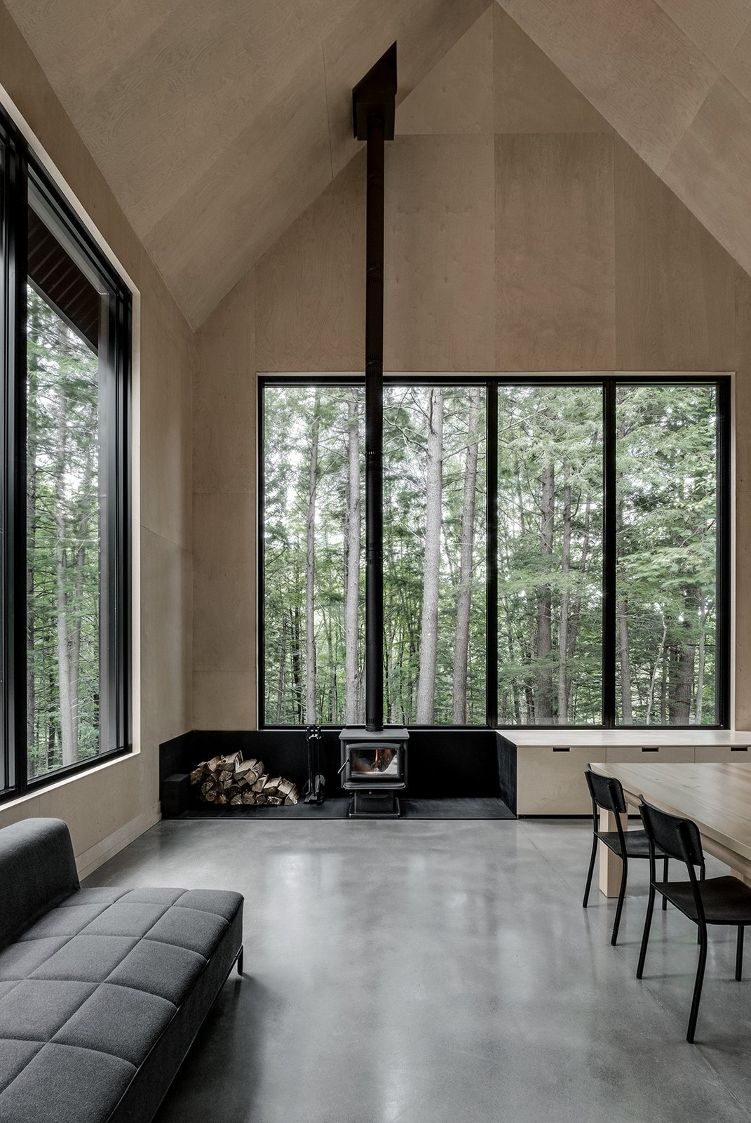 Living Room, Sofa, Wood Burning Fireplace, Concrete Floor, Storage, Chair, and Table  Photo 8 of 17 in A Lofty Nature Retreat in Quebec Inspired by Nordic Architecture