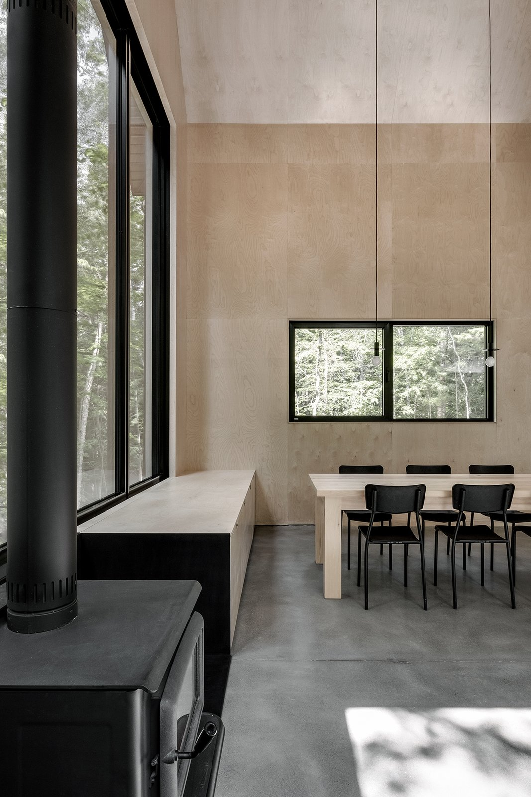 Dining Room, Wood Burning Fireplace, Concrete Floor, Ceiling Lighting, Chair, Table, and Storage  Best Photos from A Lofty Nature Retreat in Quebec Inspired by Nordic Architecture