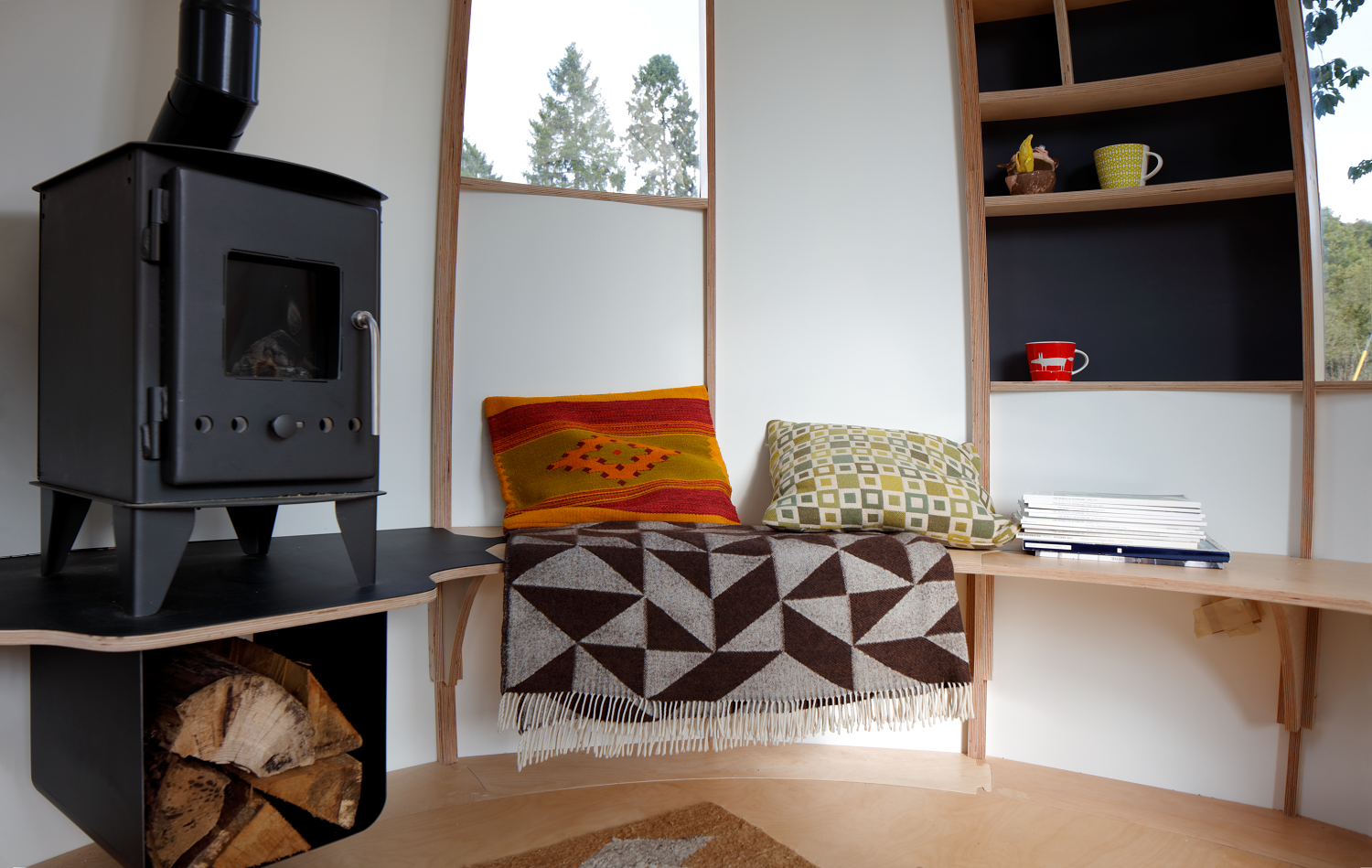 Living Room, Bench, Shelves, Light Hardwood Floor, and Wood Burning Fireplace  Photo 11 of 16 in You Can Buy Your Very Own Prefabricated Escape Pod