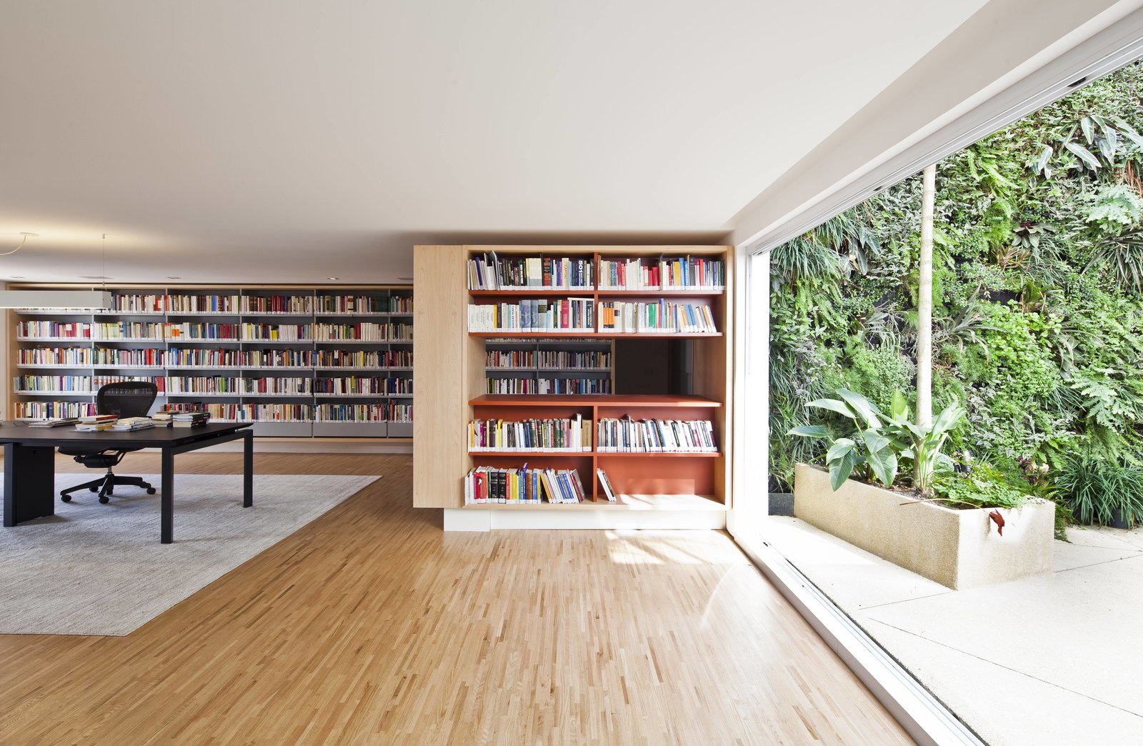 Living, Bookcase, Rug, Pendant, Chair, Desk, Light Hardwood, and Recessed  Living Recessed Bookcase Desk Photos from Living Green Walls Bring Jungle Vibes Into a Brazilian Apartment