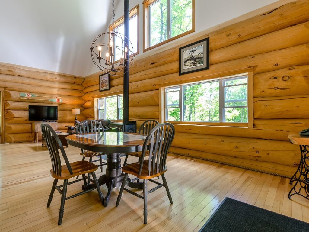 Dining Room, Chair, Table, Pendant Lighting, Wood Burning Fireplace, and Light Hardwood Floor  Photo 6 of 16 in 8 Outstanding Cabins For Rent in Canada
