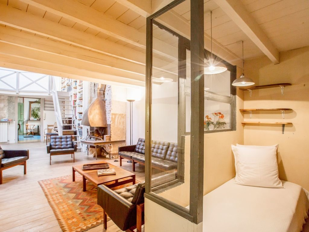 Bedroom, Bed, Pendant Lighting, Light Hardwood Floor, and Shelves  Photo 5 of 9 in 8 Charming Parisian Apartments You'll Want to Book Right Now
