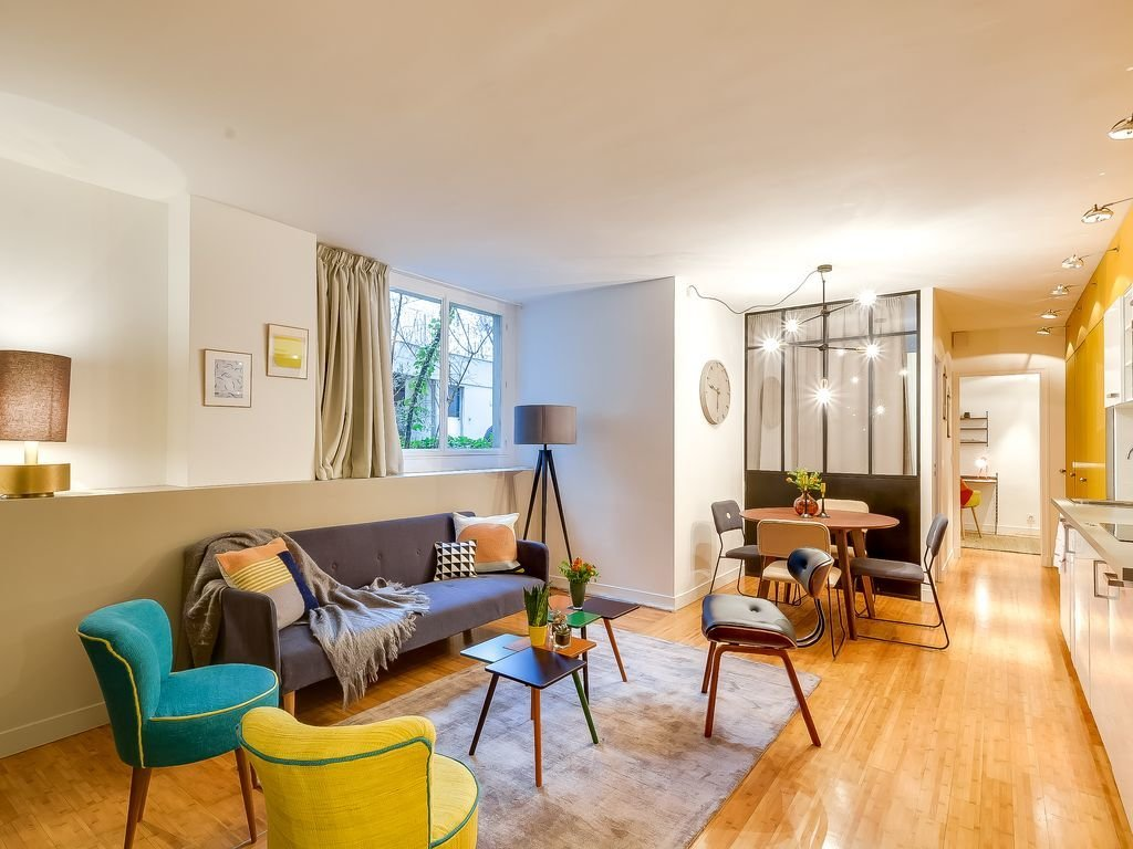 Living Room, Chair, Coffee Tables, Pendant Lighting, Sofa, and Light Hardwood Floor  Photo 7 of 9 in 8 Charming Parisian Apartments You'll Want to Book Right Now