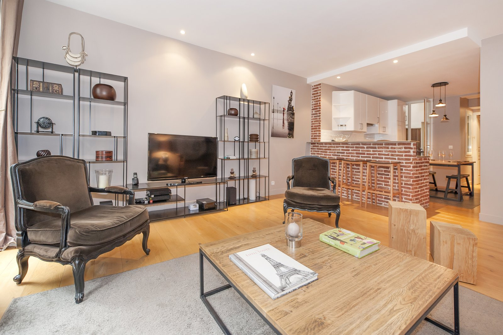 Living Room, Chair, Coffee Tables, Rug Floor, Shelves, Console Tables, Ceiling Lighting, and Light Hardwood Floor  Photo 9 of 9 in 8 Charming Parisian Apartments You'll Want to Book Right Now