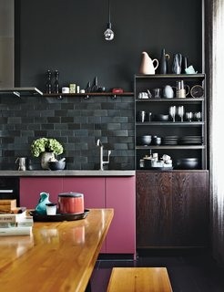 Interior designer Peter Fehrentz's pied-à-terre in Berlin has a small kitchen with rosy pink kitchen cabinets that fit right in with the rest of the apartment's chic and eclectic décor.