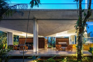 For this residence ensconced in nature near Brazil's Itamambuca Beach, São Paulo studio Arquitetura Gui Mattos used a concrete slab for the roof structure, which takes the form of an inverted prism, with its tip pointing downwards from the center of the ceiling.