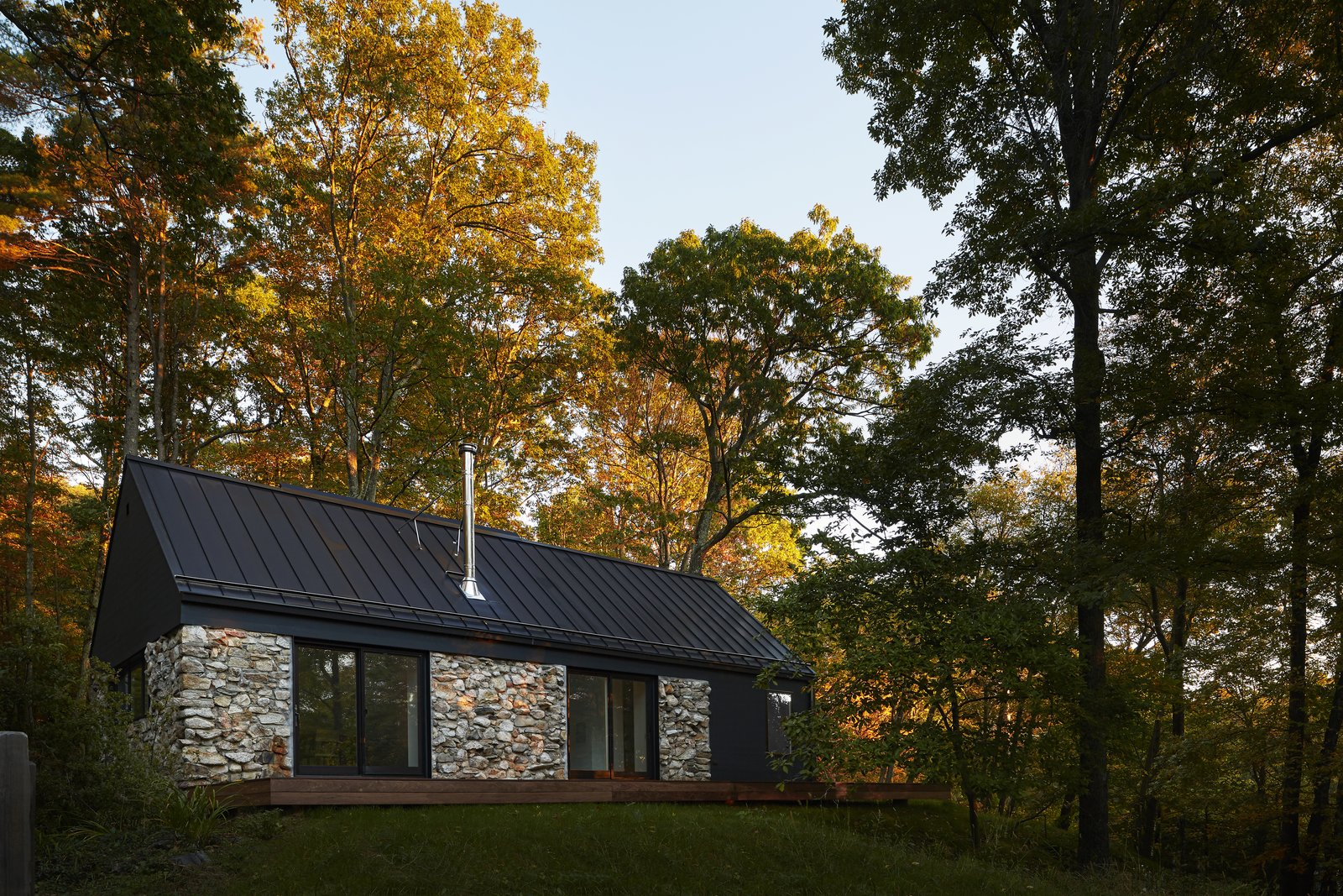 Exterior, House Building Type, Stone Siding Material, Cabin Building Type, Metal Roof Material, Gable RoofLine, and Wood Siding Material  Photo 1 of 13 in A Minimalist Retreat Rises From Old Stone Walls in Hudson Valley
