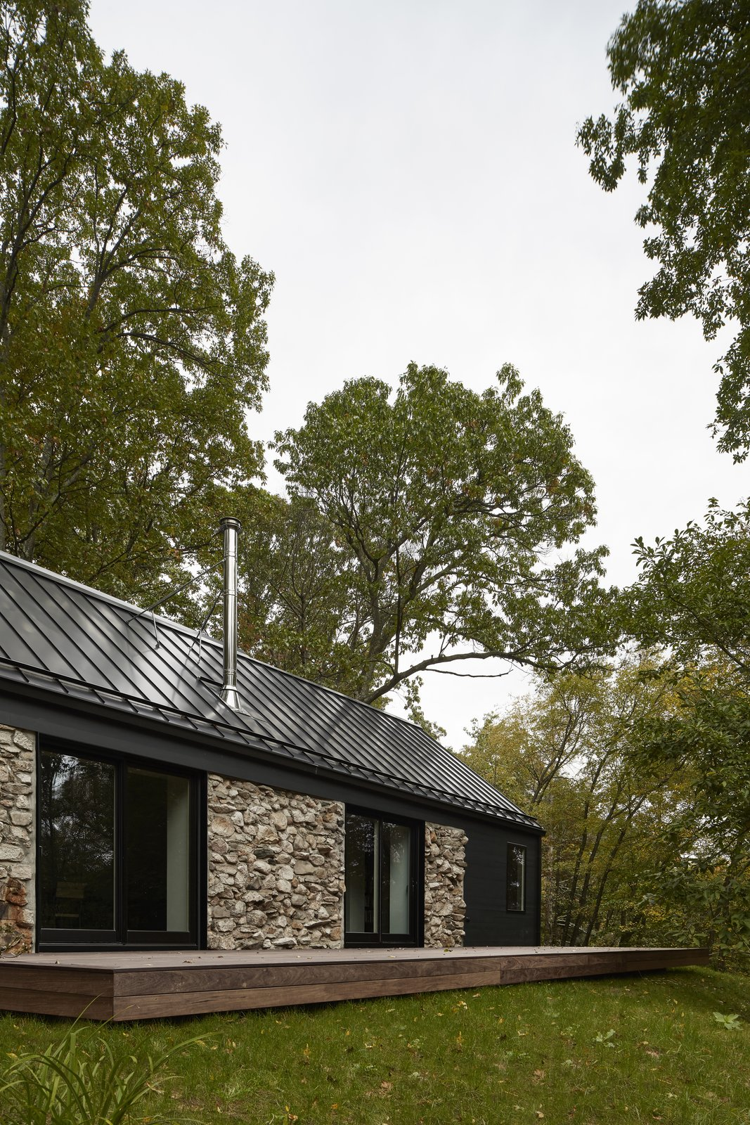Exterior, Cabin Building Type, House Building Type, Metal Roof Material, Stone Siding Material, Gable RoofLine, and Wood Siding Material  Photo 2 of 13 in A Minimalist Retreat Rises From Old Stone Walls in Hudson Valley