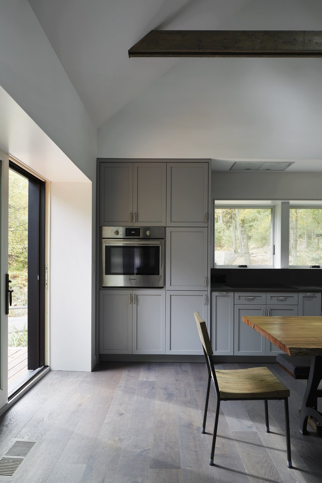 Kitchen, Light Hardwood Floor, Wall Oven, Ceiling Lighting, and White Cabinet  Photo 8 of 13 in A Minimalist Retreat Rises From Old Stone Walls in Hudson Valley
