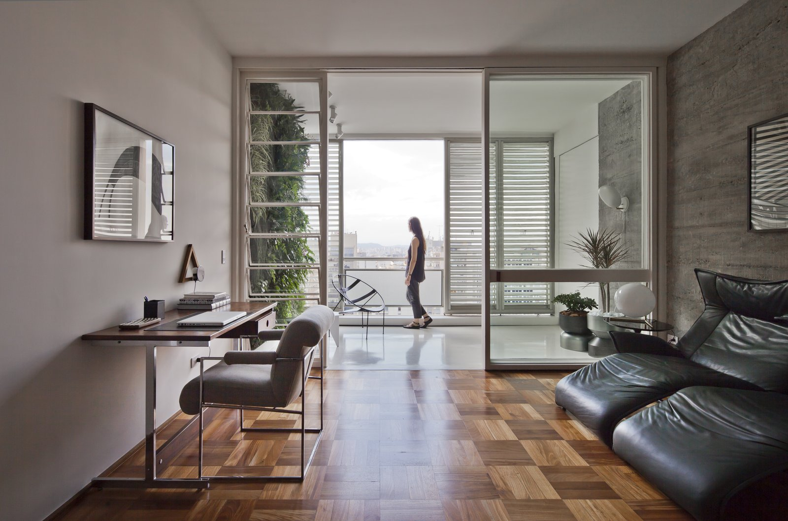 Living, Chair, Medium Hardwood, End Tables, Table, Lamps, Desk, Wall, and Recliner  Living Desk Wall Photos from This Renovated Pad in São Paulo's Iconic Lausanne Building Is a Breath of Fresh Air