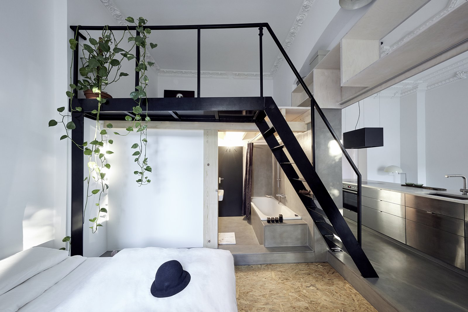Bedroom, Concrete Floor, Bed, Plywood Floor, and Pendant Lighting  Best Photos from 8 Berlin Apartments to Book That Rival the City's Level of Cool