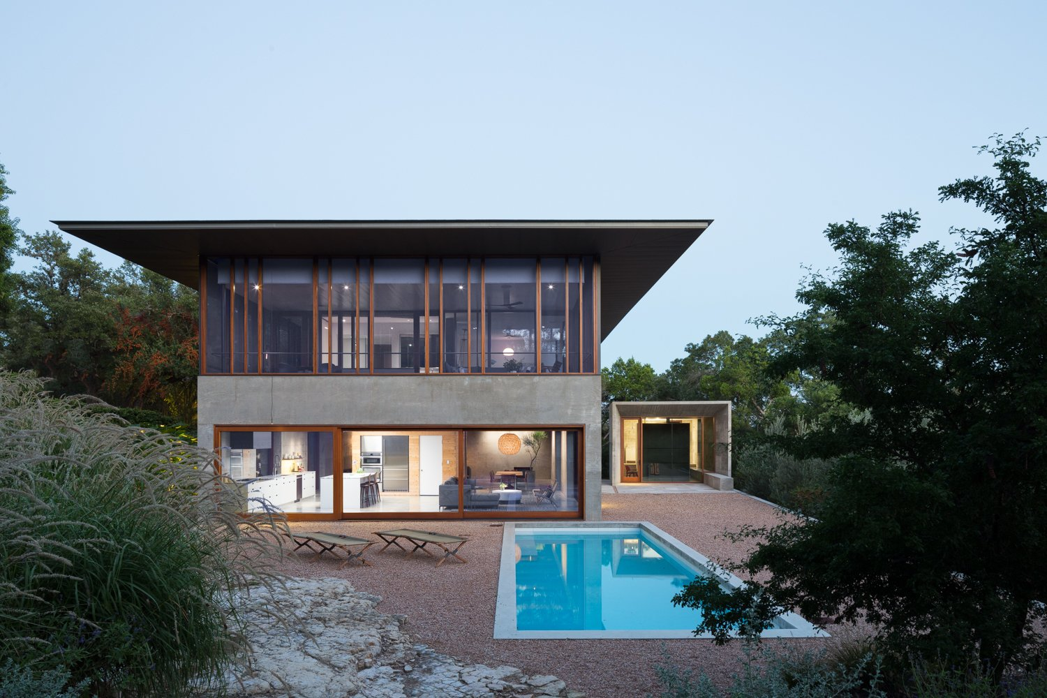 Outdoor, Shrubs, Hardscapes, Back Yard, Trees, and Swimming  Best Outdoor Shrubs Swimming Photos from A Dramatic Roof and Board-Formed Concrete Keep This Texas Residence Cool