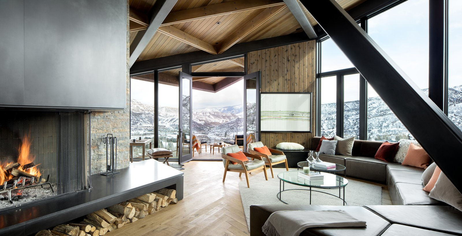 Living Room, Sectional, Coffee Tables, Chair, Standard Layout Fireplace, Rug Floor, Recessed Lighting, Ottomans, Wood Burning Fireplace, and Medium Hardwood Floor  Photo 4 of 16 in An Angular Mountain Retreat in Colorado Captures Breathtaking Views