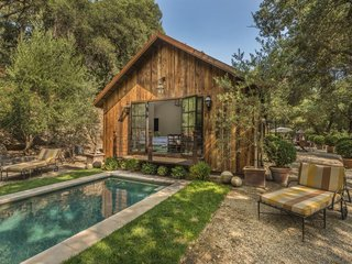 This Napa Valley farmhouse in Saint Helena has a pool, and an outdoor dining area with a fountain and a rock fireplace.