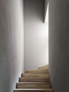 A small staircase winds between two narrow walls and up towards the attic.