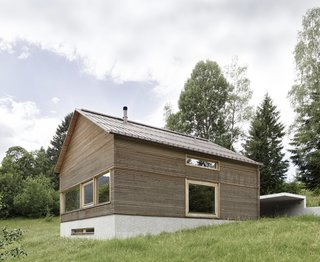"Guided by the region's traditional alpine farmhouses, Austrian firm Innauer Matt Architekten designed the house as a simple wooden building resting atop a solid, reinforced concrete plinth. The striking pitched roof is made of copper with its gable looking down towards the valley, and horizontal larch cladding was used for the façade to give the house an interesting ribbed texture with deep grooves. <span style=""color: rgb(204, 204, 204); font-size: 13px;"">Courtesy of Adolf Bereuter</span>"