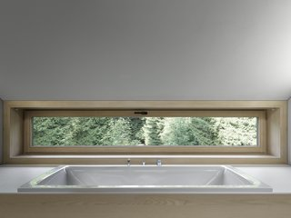 A bathtub that looks out to views of the trees