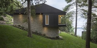 The house dips down the slope, creating the impression of being half buried in the ground.