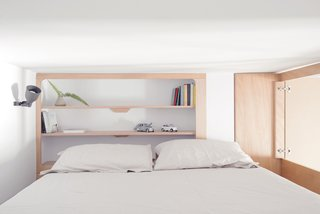 The cabin-like bedroom contains a king-size bed and minimalist, built-in shelves.