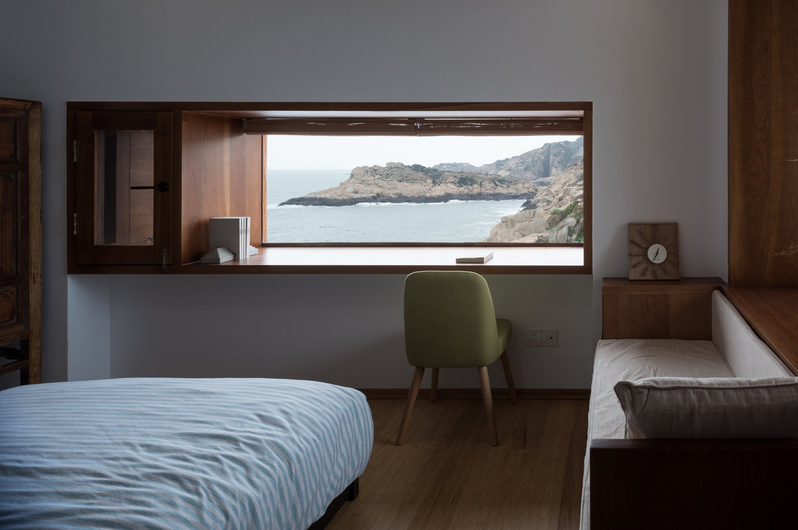 A window nook is used as a study desk in the bedroom.