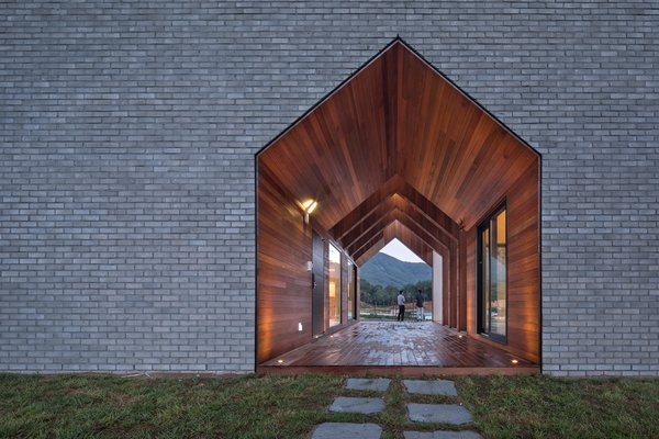 Fitted on all sides with warm wood, this double-height, gable-shaped passageway serves as the entrance to the house.