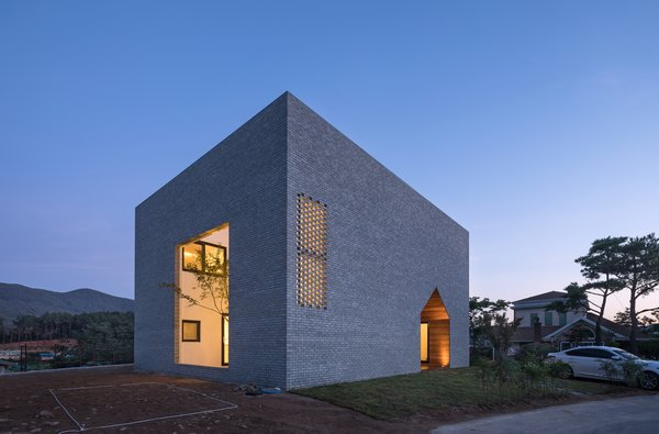 A cube-shaped home in South Korea with the form of a small, gabled house cut out to create a wide passageway