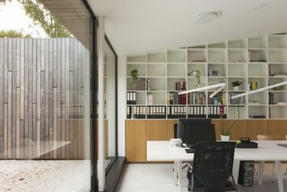 The study area has built-in shelves and a Joyn Conference Bench by Vitra.