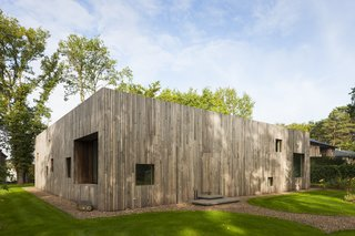 Several square perforations of varied sizes along the wooden facade serve as windows.
