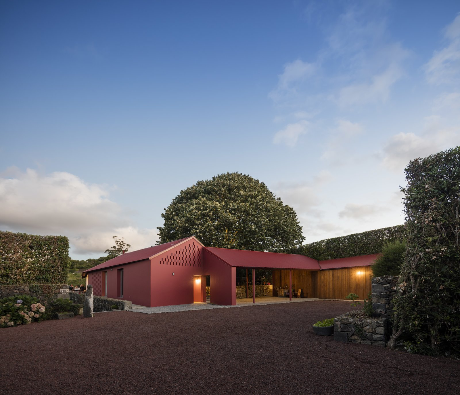 Exterior, House Building Type, Shed RoofLine, Gable RoofLine, and Metal Roof Material  Photo 3 of 14 in A Bright Red Island Residence Embraces a Linden Tree