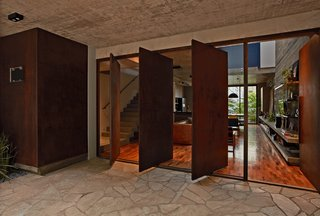 This Slender Concrete Home in Brazil Feels Like an Urban Jungle - Photo 3 of 13 - Four pivoting Cor-Ten steel doors help with cross ventilation.