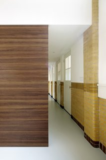 A wooden box, which houses a walk-in closet and stairs to the bedrooms, acts as a partition that dissects the hallway.