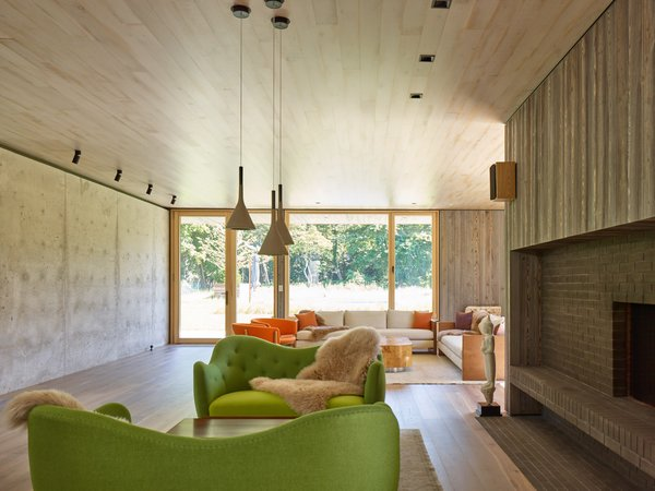 A green Finnjuhl sofa and table at fireplace, and pendants from Foscarini.