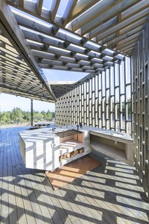The latticework of the screens allows light to enter the porches, casting ever-shifting shadows as the sun moves across the house through the day. On the side porch is an outdoor grilling area that's perfect for entertaining. There are also multi-level benches arranged around the fire pit where friends family can gather.
