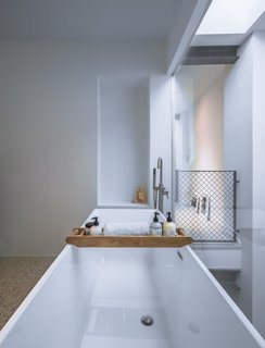 The bathtub rests along a fully glazed wall, and looks down to the living area below.