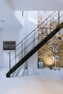 Exposed brick walls work with a black steel staircase and polished concrete floors to give the interior an edgy and modern atmosphere.