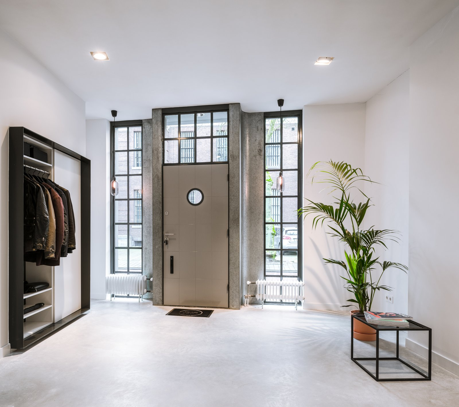 Doors, Metal, Swing Door Type, and Exterior Glass windows help connect the entrance foyer to the street outdoors.  Photo 3 of 14 in A 19th-Century Dutch Workshop Is Now a Stunning, Spacious Loft