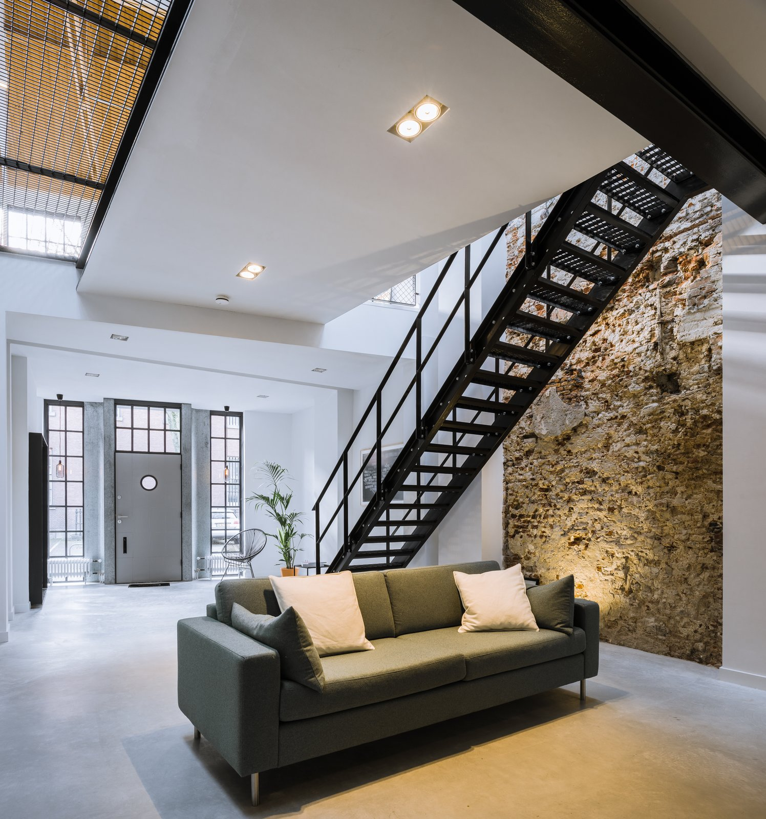 Living Room, Recessed Lighting, Concrete Floor, and Sofa The existing steel beams and wooden floor structure of the upper level were retained.  Photo 5 of 14 in A 19th-Century Dutch Workshop Is Now a Stunning, Spacious Loft