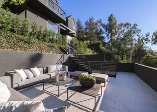 An outdoor terrace on the slope of the property offers additional lounging and entertainment areas.