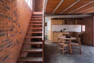 A simple material palette of brick, concrete, tiles, and wood gives the home a warm, contemporary atmosphere.