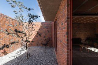 A courtyard helps isolate the interior of the house visually and acoustically from its urban surroundings, and provides a large opening on the envelope of the house, where light and shadows enhance the colors and textures of the building throughout the day.