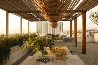 The terrace area features a reed and metal pergola structure designed by PSS Design Cult.
