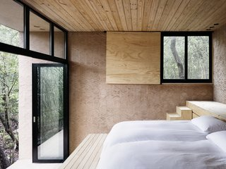 Rammed earth, brick, and wood give the bedroom a rustic, minimalist look.