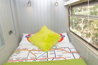 This Double-Decker Bus Offers an Eclectic Glamping Experience - Photo 6 of 12 - A small bedroom that looks out to the forest.