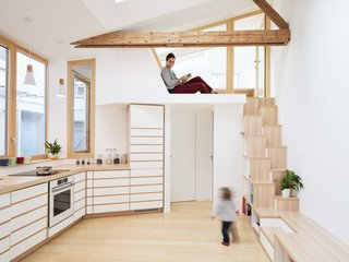 "In Paris, a painter's granddaughter turns a 484-square-foot studio into a minimalist family home that abounds with smart storage and integrated furniture. A reading nook in front of the ""cabin"" workspace is at the top of the stairs."